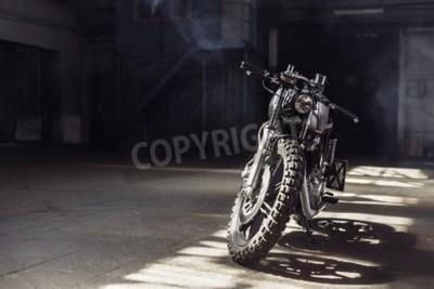 Image Moto vintage debout dans un bâtiment sombre dans les rayons du soleil. Couleurs tonique. Vue de face