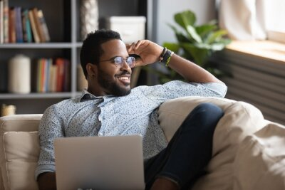Image Multiracial freelance guy distracted from job study, looking at window.