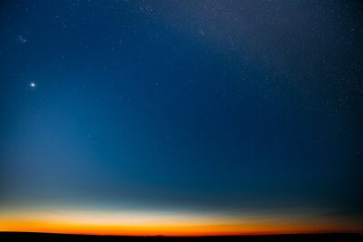 Night Starry Sky With Glowing Stars Above Countryside Field Landscape In Early Spring. Bright Glow Of Planet Venus In Sky Among The Stars. Sky In Warm Lights Of Evening Sunset Dawn Or Morning Sunrise