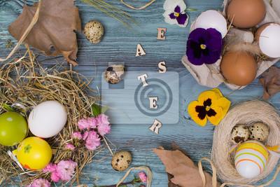 Image Oeufs de Pâques, fleurs et autres décorations sur la table en bois  bleu.