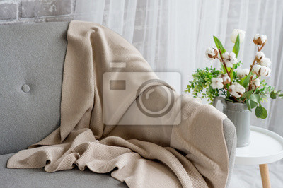 Image On the gray sofa there is a beige plaid trimmed with lace. Next is a chair, on it a vase with white tulip and branches of cotton.