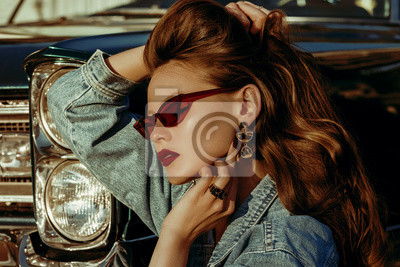 Image Outdoor close up fashion portrait of young beautiful fashionable woman with long luxury hair, wearing red cat eye sunglasses, denim jacket, leopard print earrings, posing near retro car, at the sunset