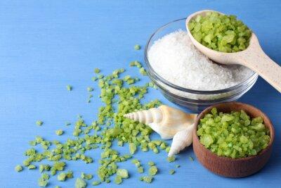 Image Parfumé de sel de mer verte et blanche est dans un bol en verre et en bois bowl.Scattered autour du sel de mer verte avec des coquillages sur une table en bois bleu avec des coquillages