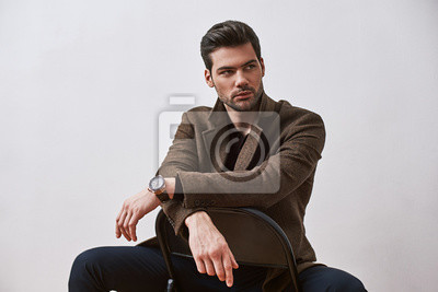 Image Perfect style. Stylish dark-haired man sitting on a chair and looking away isolated over white studio background