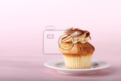 petit gâteau avec glaçage sur assiette blanche