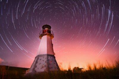 Image phare avec un ciel de nuit à étoiles d'arrière-plan des pistes