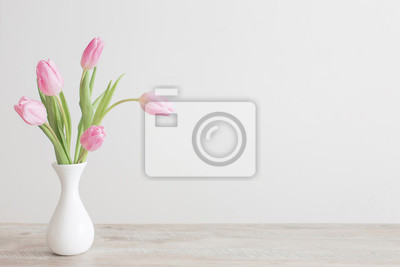 Image pink tulips in white ceramic vase on wooden table on background white wall