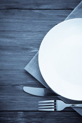 Image plaque blanche, couteau et une fourchette sur le bois