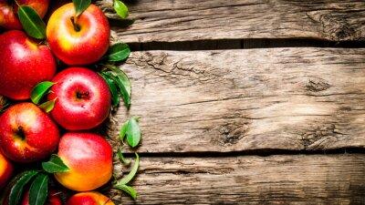 Image Pommes rouges fraîches avec des feuilles vertes sur la table en bois.