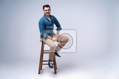 Image Portrait de toute la longueur d'un jeune homme attrayant en chemise de jeans, assis sur une chaise sur fond gris.