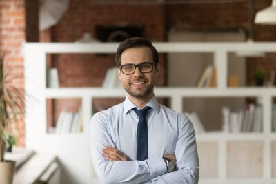 Image Portrait of sincere smiling confident young 30s male ceo executive manager in eyeglasses and formal wear posing in modern office room, looking at camera, successful corporate career opportunity.