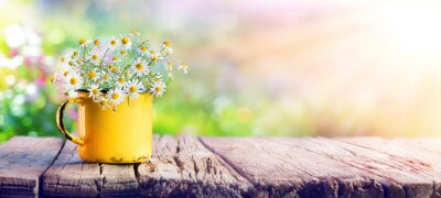 Image Printemps - fleurs de camomille dans une tasse de thé sur une table en bois dans le jardin