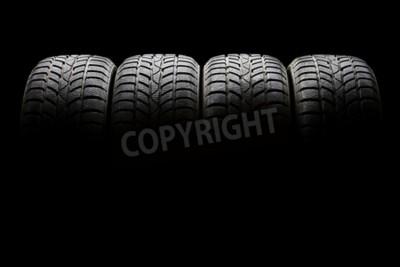 Image Prise de vue en studio d'un ensemble de quatre pneus de voiture noire alignés horizontalement dans une ambiance sombre sur fond noir