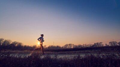 Image Ragazza atletica allena all'aperto su terra di sera