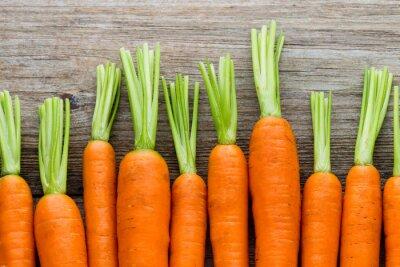 Image Rameau de carottes fraîches sur fond de bois rustique.