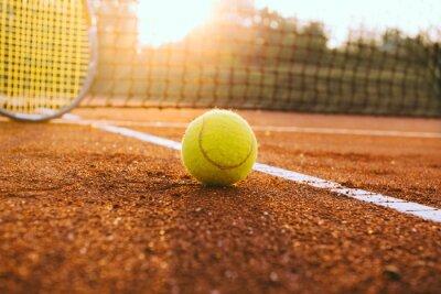 Image Raquette de tennis et une balle sur un court en terre battue