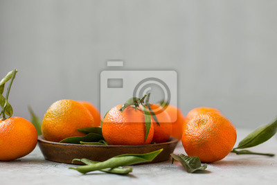 Ripe mandarines fruits with leaves, fresh citrus fruits on concrete background with copy space