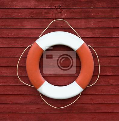 Rouge et blanc bouée de sauvetage accroché sur le côté d'un bateau en bois
