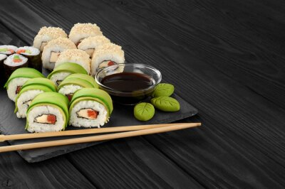 Image Rouleaux de sushi avec des graines d'avocat, de saumon et de sésame sur le plateau d'ardoise.
