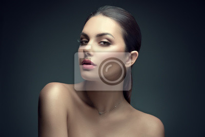 Image Sexy beauty brunette woman with perfect makeup. Beauty girl's face on dark background. Skincare