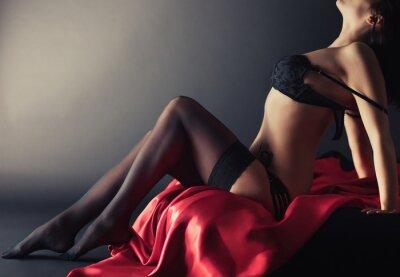 Image Sexy jeune femme brune en lingerie sensuelle noire et en bas pose sur le lit en studio.