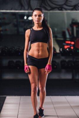 Sexy jeune femme posant à la salle de gym