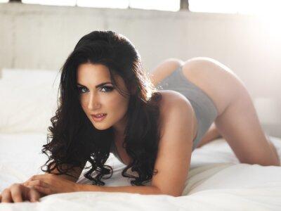 Image Sexy modèle sur lit brillamment éclairé dans pose érotique