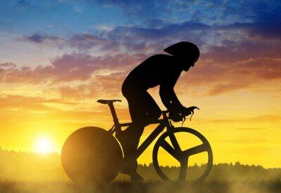 Image Silhouette d'un cycliste sur un vélo de course sur route au coucher du soleil.