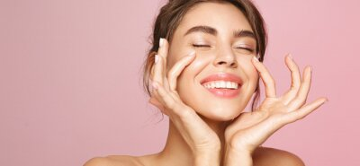 Image Skin care. Woman with beauty face touching healthy facial skin portrait. Beautiful smiling girl model with natural makeup touching glowing hydrated skin on pink background closeup