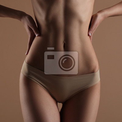 Image Skinny young woman in lingerie holds her hands on her waist