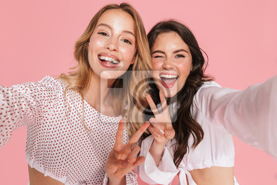 Image Smiling friends women posing isolated over pink wall background take selfie by camera.