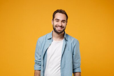 Image Smiling handsome young bearded man in casual blue shirt posing isolated on yellow orange wall background studio portrait. People sincere emotions lifestyle concept. Mock up copy space. Looking camera.