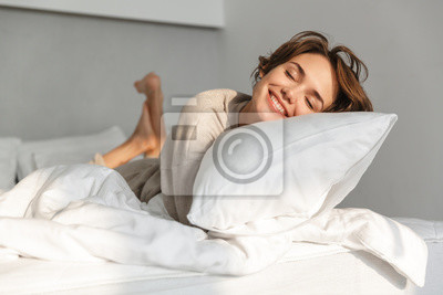 Image Smiling young girl relaxing in bed