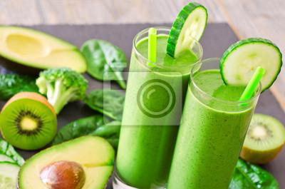 Smoothie vert dans des verres à l'avocat, le kiwi et les épinards