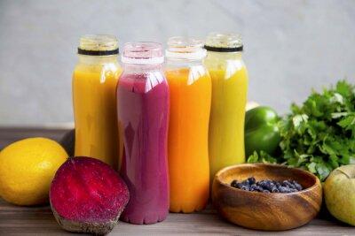 Smoothies biologiques frais dans des bouteilles avec des fruits et des légumes