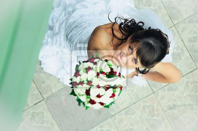 souriant mariée avec un bouquet de fleurs à regarder vers le haut