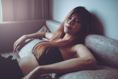 Image Sporty Asian woman is posing cool on sofa with seductive active black clothing for Street Girl fashion style.