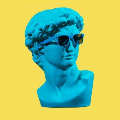 Image Statue. Earphone. Isolated. Gypsum statue of David's head. Man. Creative. Plaster statue of David's head in blue sunglasses. Minimal concept art.