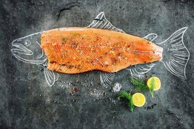 Image Steak de poisson de saumon cru avec des ingrédients comme le citron, le poivre, le sel de mer et l'aneth sur le tableau noir, l'image esquissée à la craie de poisson de saumon avec steak