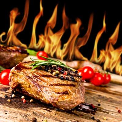 Image Steaks de bœuf grillé avec des flammes sur le fond