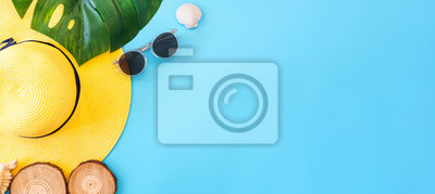 Image summer blue banner with yellow hat ,sunglasses,seashell and monstera leaf on blue background top view.