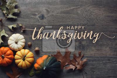 Image Texte de voeux Happy Thanksgiving avec citrouilles colorées, courges et feuilles sur fond en bois foncé