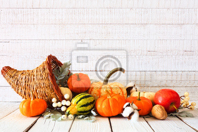 Image Thanksgiving cornucopia filled with autumn vegetables and pumpkins against a rustic white wood background