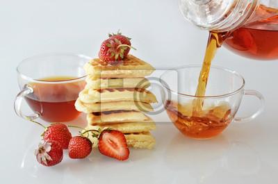 Thé se renversant dans une tasse avec gaufres et fraises
