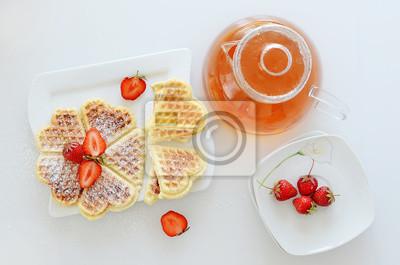 Théière avec des gaufres sur la plaque et fraises