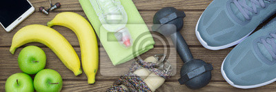 Image Top view of Healthy lifestyle concept, sport equipments and fresh foods on wood background.  Web Banner.
