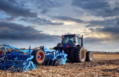 Image Tracteur travaillant sur le terrain au coucher du soleil