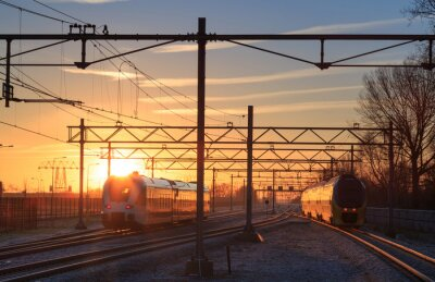 Image Trains leaving a station during a winter sunrise.
