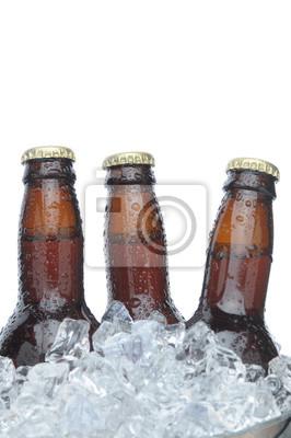 Trois bouteilles brunes de bière dans la glace