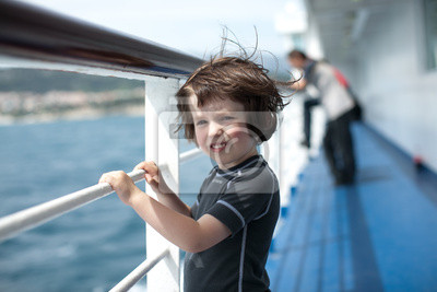 un enfant heureux sur le ferry face à la mer
